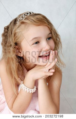 Girl of eight y.o. with blond hair grey eyes and genuinely smiling in a light-pink dress on light background.