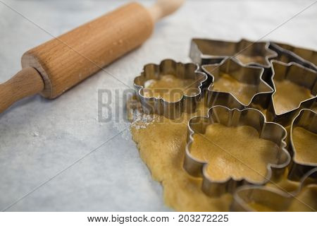 Close up of various pastry cutters over dough on wax paper