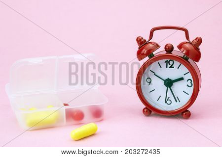 Red pharmaceutical pills tablets and yellow capsules spilling out of daily pill box with red alarm clock. Medical conceptual photo pharmacy theme
