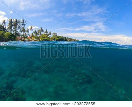Double landscape. Blue sea and sky. Seascape split photo. Double seaview. Underwater coral reef. Above and below waterline border. Exotic seashore. Coral reef and green island beach. Shallow seawater
