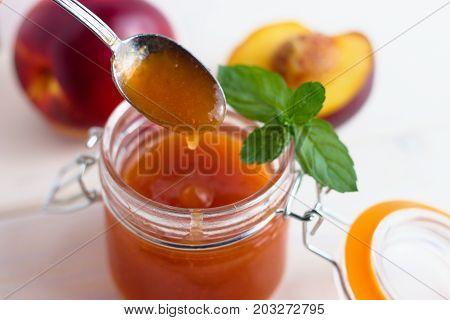 Peach jam served by teaspoon from glass jar
