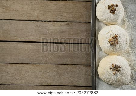 Close up of unbaked cookies in baking sheet on wooden table