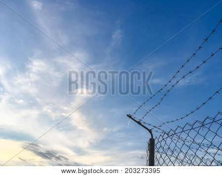 Barbed wire against the blue sky, imprisonment concept, copy space