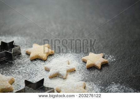 Close up of star shape cookies with pastry cutter on gray table