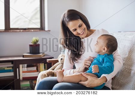 Happy mother playing with her baby on lap at home. Infant sitting on mother's lap playing and looking at her. Young smiling woman babysitting cute toddler.
