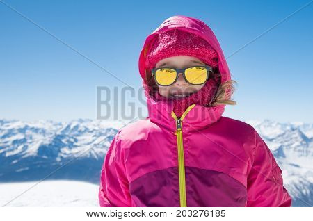 Portrait of happy little girl with sunglasses enjoy ski outdoor. Active sportive girl in ski gear on winter background. Smiling cute girl has fun in snow.