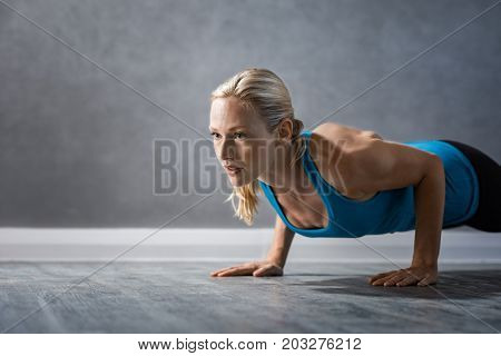 Young beautiful sportive girl doing exercise for abs. Fit woman doing push ups at the gym. Determined woman doing pushups on the floor and looking away with copy space.