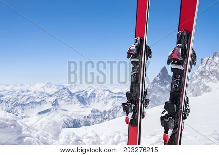Pair of red skis standing in snow with copy space. Closeup of the ski touring equipments on the top of the mountain with copy space. Winter and extreme sport concept.