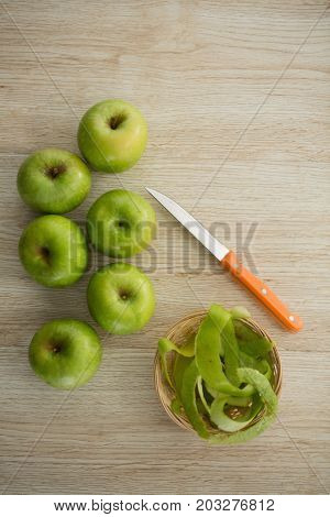 Overhead view of granny smith apples by peel and kitchen knife on wooden table