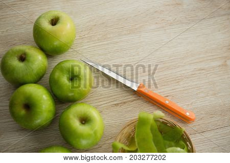 Close up of granny smith apples by peel and kitchen knife on wooden table