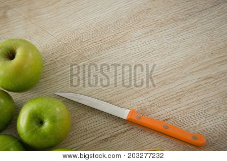 Overhead view of granny smith apple by kitchen knife on wooden table