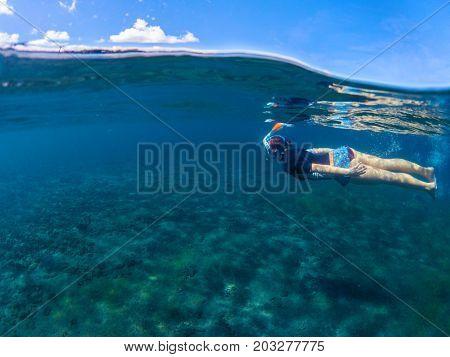 Woman swimming in blue sea. Snorkeling girl in full-face snorkeling mask. Split landscape above and below waterline. Seashore underwater photo. Active seaside vacation. Water sport in tropical sea