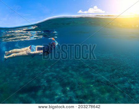 Woman swimming in blue sea. Snorkeling girl in full-face snorkeling mask. Split landscape above and below waterline. Seashore underwater photo. Sunny seaside fun activity. Water sport in tropical sea