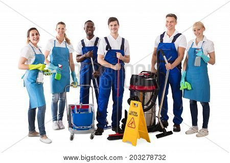 Portrait Of Happy Multiethnic Janitors Holding Cleaning Equipment Against White Background