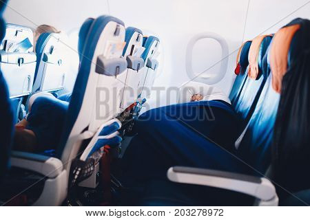passenger of the plane lies on an armchair and sleeps