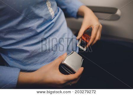 Girl passenger fastening seat while belt sitting on airplane