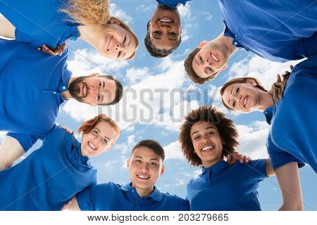 Low Angle View Of Smiling Multiracial Janitors Forming Huddle