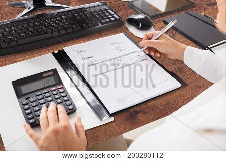 Close-up Of A Businessperson's Hand Calculating Invoice In Office