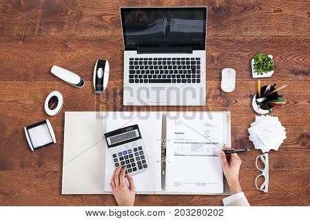 High Angle View Of A Businessperson Analyzing Bill In Office Over Desk