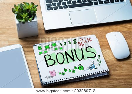 Bonus And Employee Compensation Concept In Notepad At Desk