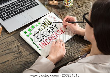 Woman Drawing Salary Increase Words In Notepad