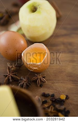 High angle view of broken egg with granny smith apple on wooden table