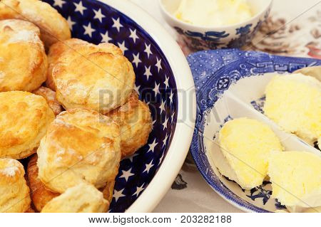 Bowl with many homemade scones surrounded by small bowls with clotted cream. Traditional English cream tea.
