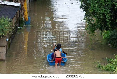 People rowing a boat through a flooded street in Thailand