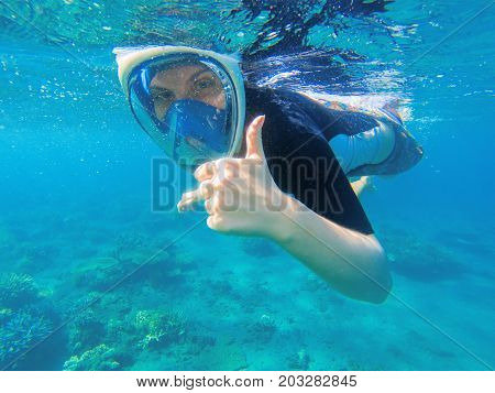 Snorkeling woman shows thumb. Snorkeling girl in full-face snorkeling mask. Coral reef in shallow sea. Snorkel undersea. Seashore underwater photo. Active seaside vacation. Water sport in tropical sea