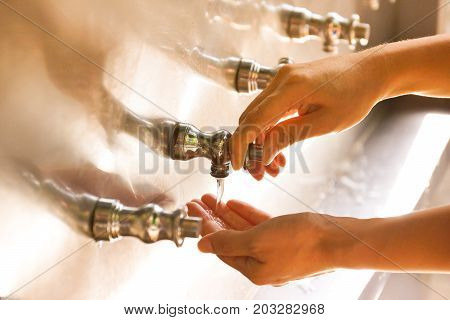 Hand pressing a faucet button at a water cooler   Water consumption concept