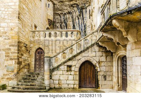 built under a mountain of rocks is located this the shrine of rocamadour place of built under a mountain of rocks is located this the shrine of rocamadour place of pilgrimage in the image we see an external courtyard of the same in the image we see an inn