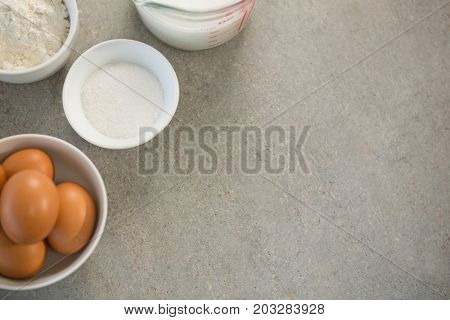 Eggs with sugar and flour in bowls on table