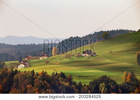 View Of Austrian Village On Mountain Hills In Alps. Beautiful Mountain Rural Autumn Landscape.