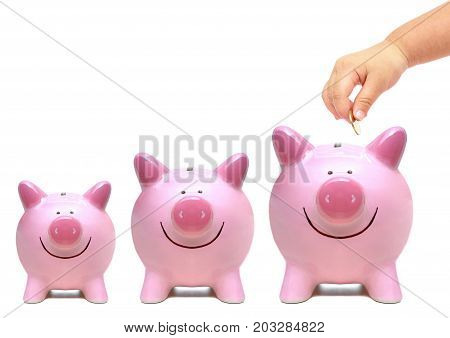 Hand of a young baby giving golden coin to three piggy banks with different sizes - Young generation start saving concept