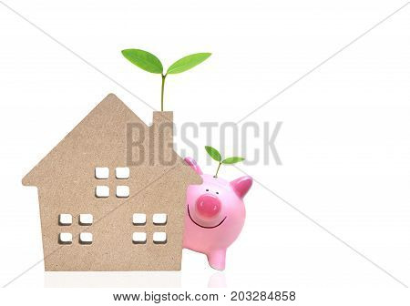 A pink piggy bank and a wooden house with green trees / Saving money for buying eco-house concept