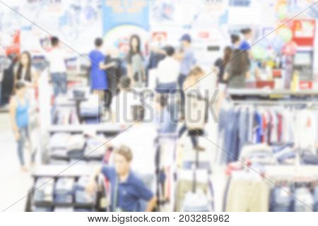 Shopping mall during seasonal sale indoor blurry photo. Department store selling clothes. Fashion shopping blurred background. Shopping mall interior. Customer crowd in white light. Store overcrowded