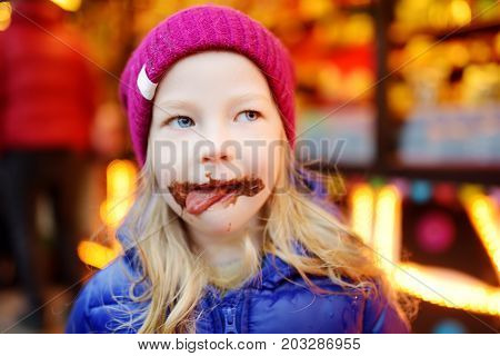 Adorable Little Girl Eating Waffle Covered With Chocolate Icing On Traditional Christmas Market