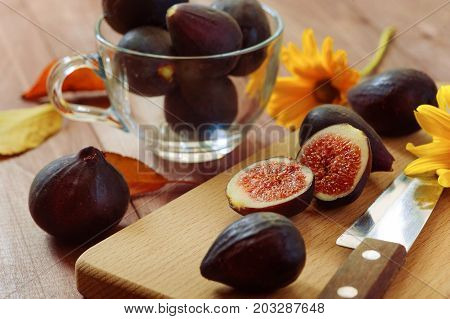 Bright autumn composition of figs, dry flowers and tree branches on wood background. Flat lay, top view