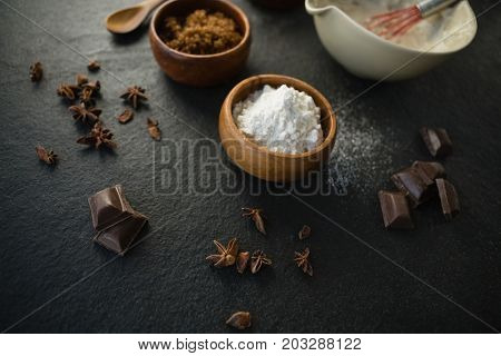High angle view of flour with spice and chocolate bars on table
