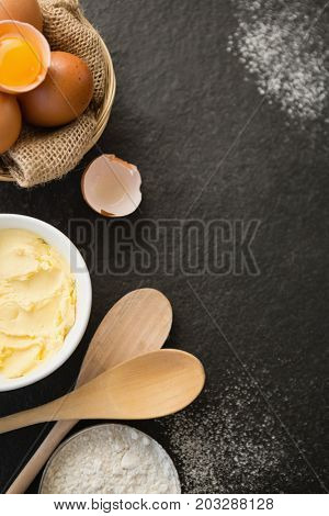 Overhead view butter by eggs in bowl on table
