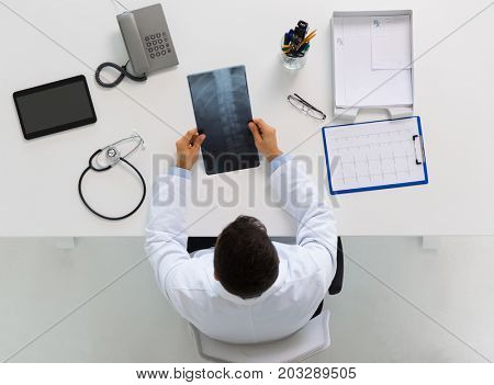 medicine, healthcare and surgery concept - doctor or surgeon with spine x-ray sitting at table