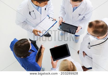 medicine, healthcare, people and cardiology concept - group of doctors with cardiogram and tablet pc computers at hospital
