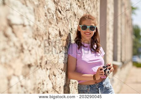 lifestyle, summer and people concept - smiling young woman or teenage girl in sunglasses with camera on city street