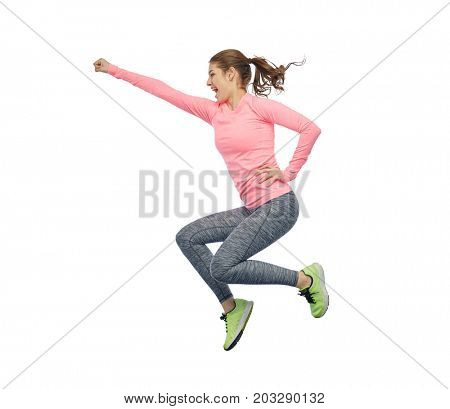 sport, fitness, motion and people concept - happy smiling young woman jumping in air and showing power gesture over white background