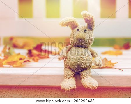 season, childhood and loneliness concept - lonely toy rabbit on bench in autumn park
