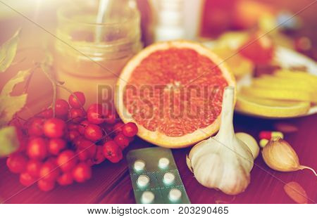 healthcare and ethnoscience concept - traditional medicine and drug pills on wooden table
