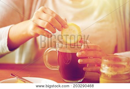 health, traditional medicine and ethnoscience concept - close up of woman adding lemon to tea cup with honey
