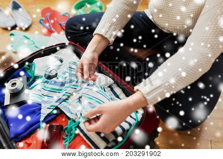 winter holidays, vacation, travel, tourism and people concept - close up of woman packing bag with bikini and summer clothes over snow
