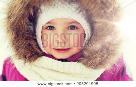 childhood, fashion, season and people concept - face of happy little kid or girl in winter clothes