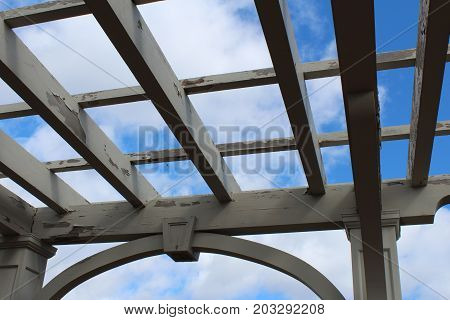 View of pergola against a blue sky, looking up